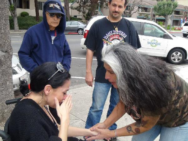 Niko Black is consoled by friends and neighbors after being illegally evicted from her home at gunpoint while in a wheelchair. Photo credit: Facebook - On Attack 4 Niko Black